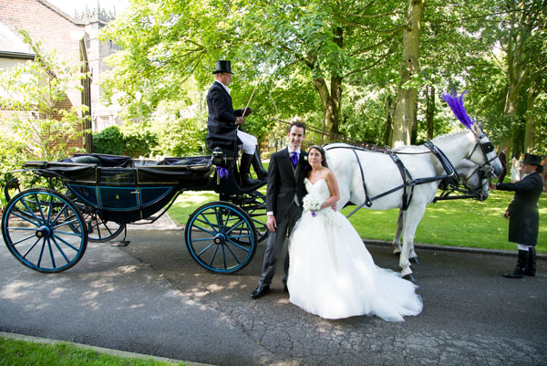 couple with horse and carriage on their wedding day