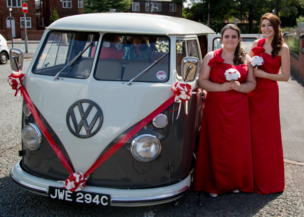 two bridesmaids in floor length red dresses with wedding camervan