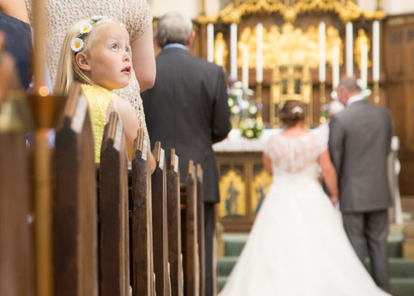 young girl looking over her shoulder during church wedding ceremony