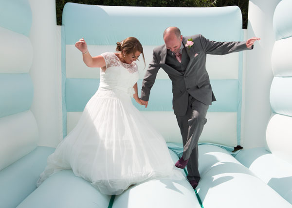 bride and groom bouncing on a blue and white bouncy castle