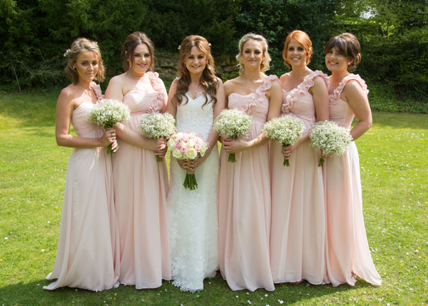bride with bridesmaids in full length pink dresses