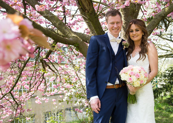 bride and groom under pink blossom tree