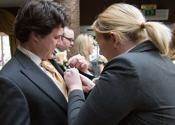 wedding coordinator fixing grooms buttonhole