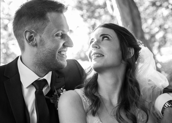 black and white bride and groom looking at each other laughing