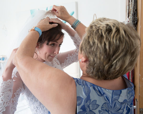 mother of the mother of the bride in blue dress fixing veil on the morning of the wedding