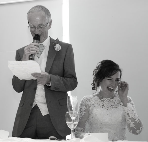 father of the bride giving a speech with bride laughing