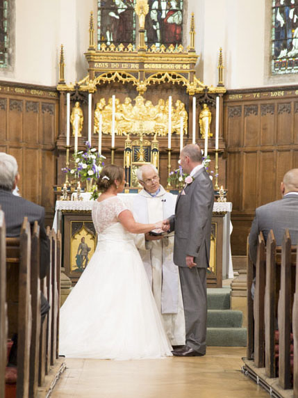 Bride and groom with binding of the hands in front of the altar in a church wedding ceremony