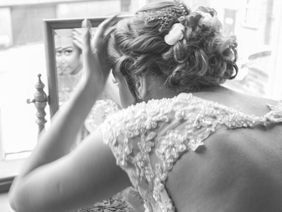 Bride checking her hair in the mirror before the wedding