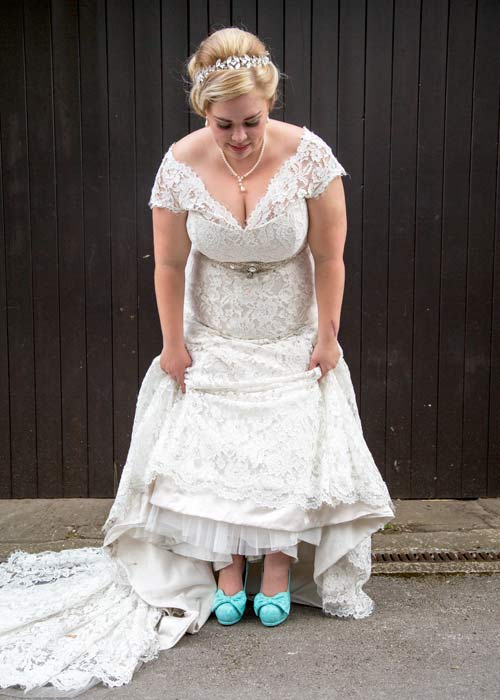 Bride holding up her dress to show blue wedding shoes