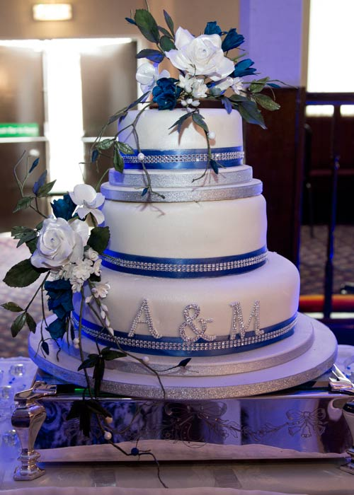 Blue and white wedding cake with diamante decorations and florestry