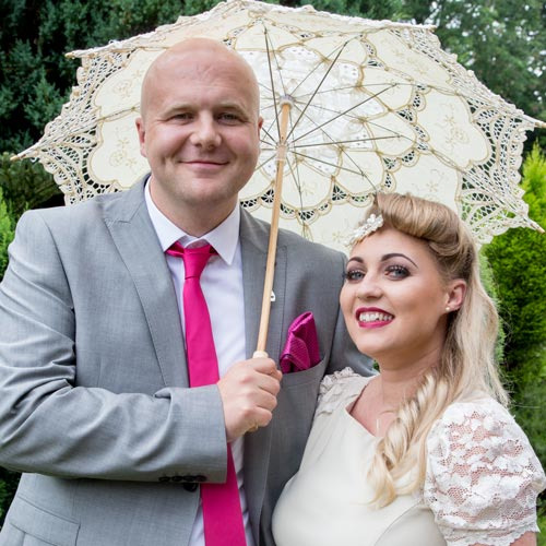 bridesmaid with her partner in a pink tie and parasol