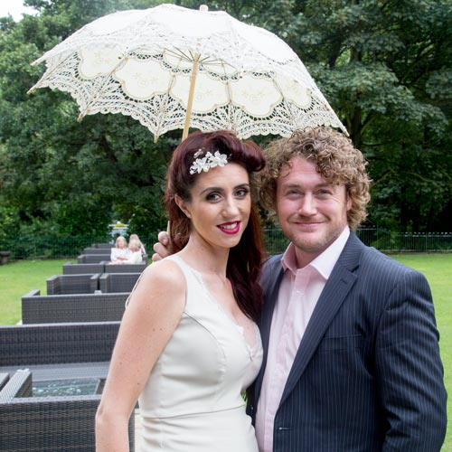 pregnant bridesmaid with her partner and parasol