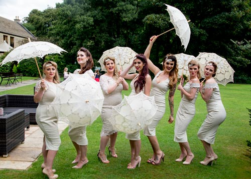 Bridesmaids dancing with parasols and bespoke dresses