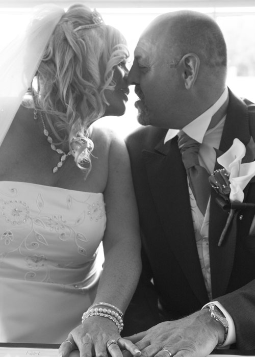 bride and groom kissing while signing register in black and white