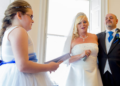 bridesmaid doing a reading at her parents wedding with parents crying in the background