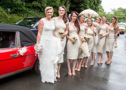 The bridal party waiting to go into the wedding venue with their bouquets and parasols in front of the Stag