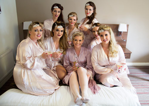 Seven bridesmaids and the bride to be in pink dressing gowns sitting on the bed with drinks