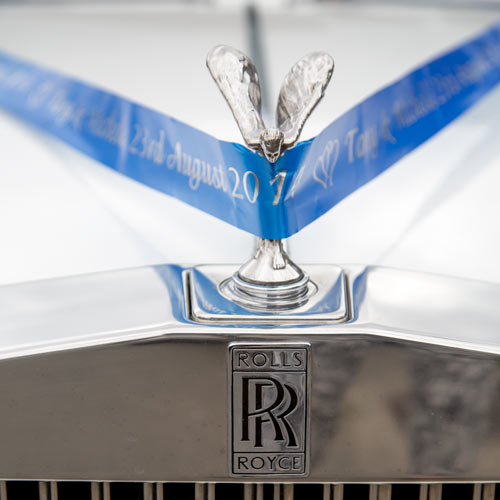 Silver rolls royce car with blue wedding ribbon