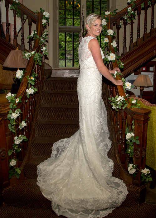 Bride wearing vintage lace dress on the stairs at whitley hall hotel sheffield