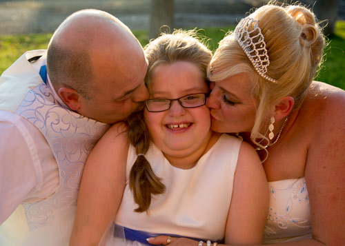 Bride and groom kissing heir daughter ourtside the wedding reception rotherham