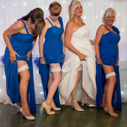 Bridesmaids and bride showing off their garters on the dancefloor in front of the top table and sparkle backdrop