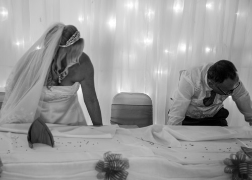 Bride and best man moving top table in black and white photography
