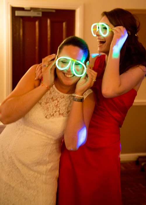 Bride and bridesmaid dancing on the dancefloor with glow stick glasses