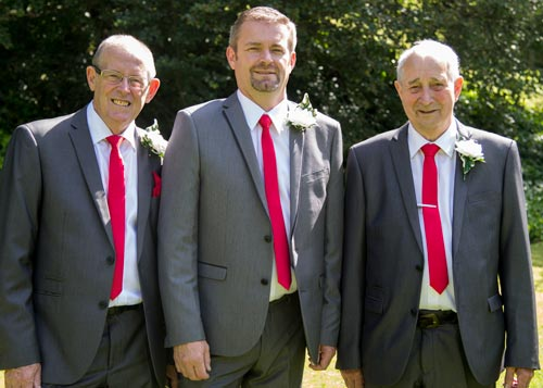 The groom with his father and the father of the bride after the ceremony wearing grey suits with red ties