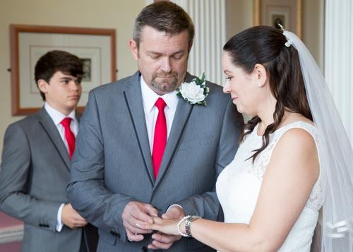 Groom wearing a red tie placing wedding ring onto the brides finger during the wedding ceremony with best man in the background
