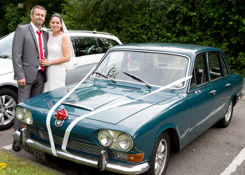 Wedding couple standing with their green wedding car on their wedding day