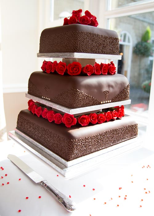 Handmade three tier wedding chocolate cake with sugarcrafted red roses and pearls attached to the side