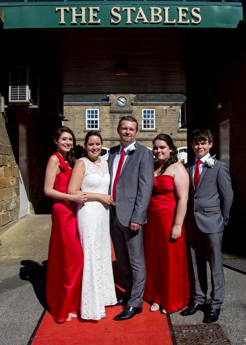 The newlyweds with their children as bridesmaids and best man standing under the main sign at the Stables doncaster