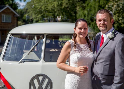 newlyweds standing next to their campervan wedding car drinking pink champagne on their wedding day