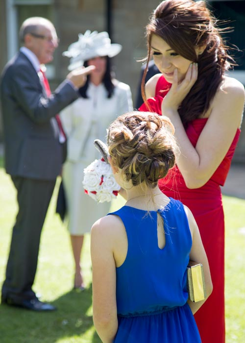 A bridesmaid in a red dress speaking to a young guest in a blue dress