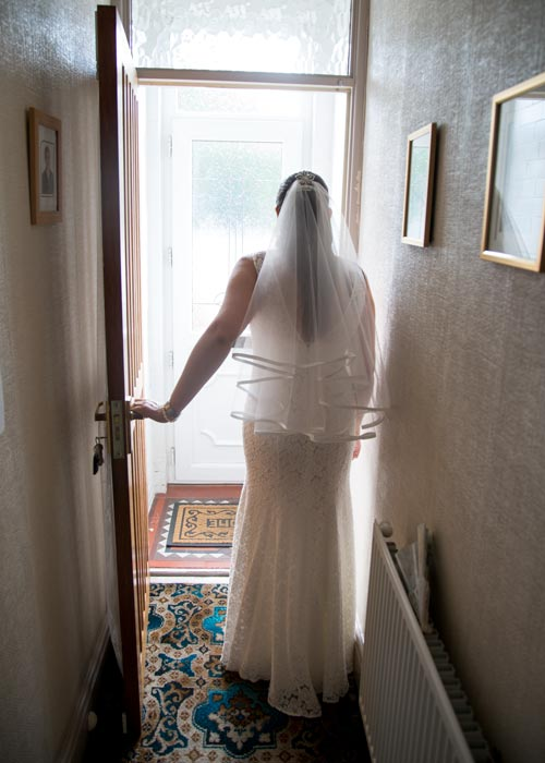Bride in her wedding dress an veil leaving her parents house for the last time before she gets married