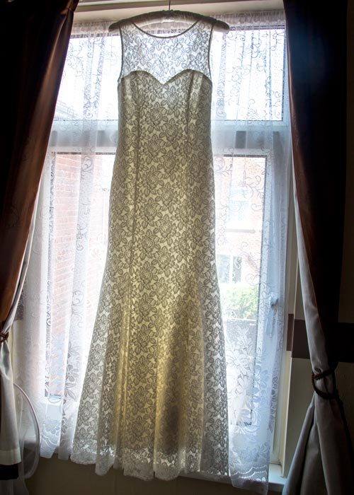 Lace wedding dress hung on a padded coathanger in front of a window before it's worn