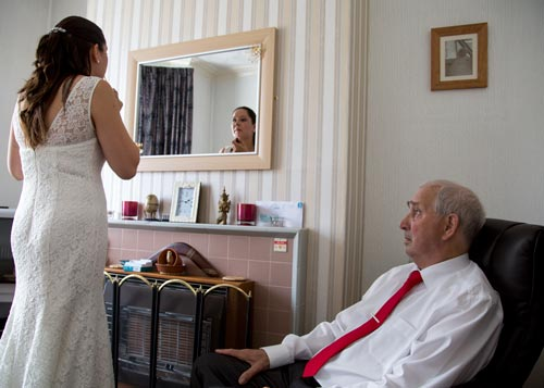 Bride looking in mirror in her parents house the morning of the wedding with her father watching from his armchair