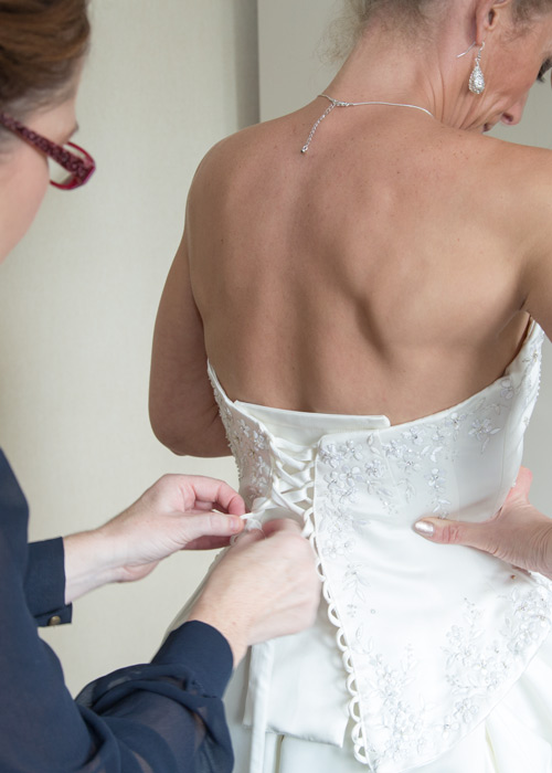 Bridesmaid fastening the wedding gown on the morning of the wedding