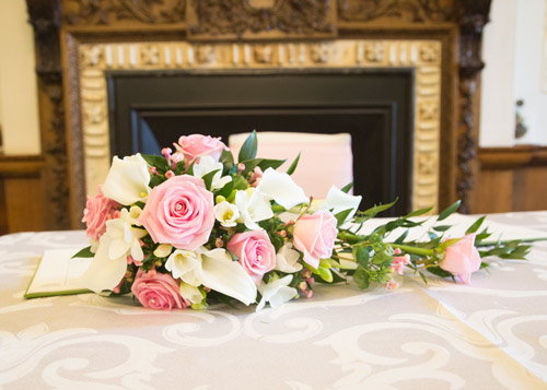 pink and white bouquet on the table in front of the fireplace at wortley hall