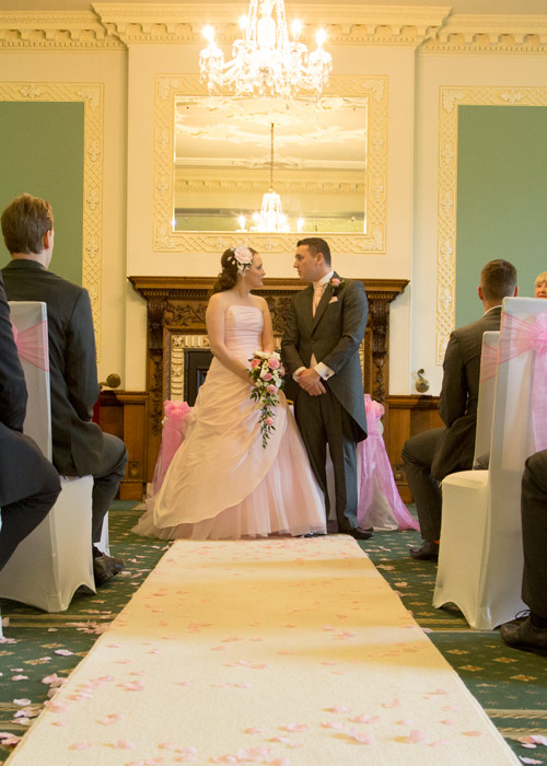 bride and groom leaving wedding ceremony room at wortley hall hotel