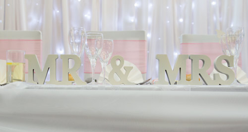 mr & mrs letters in front of a twinkle backdrop in a pink theme wedding