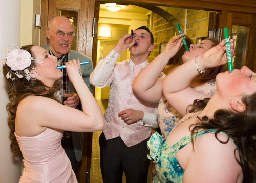 Bride groom and guests having shots during the evening reception