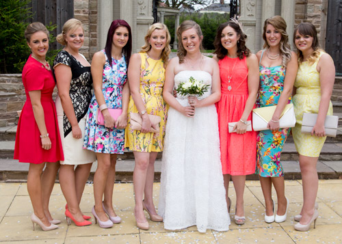 Bride and guests in bright dresses outside the secret garden holiday inn barnsley