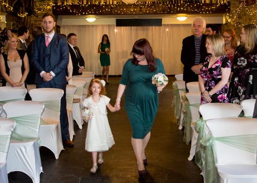 Bridesmaid walking down the aisle at Cubley Hall