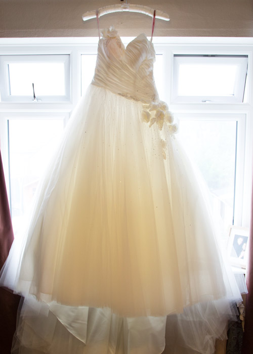the dress before its worn hanging in front of the brides window