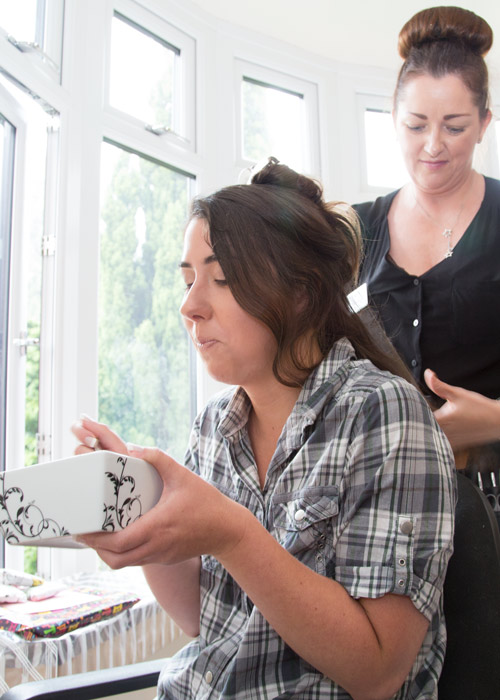 bride eating cereal while her hair is being styled on the morning of the wedding