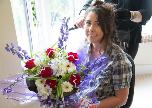 the bride with a bouquet of bright flowers sent by the groom on the morning of the wedding