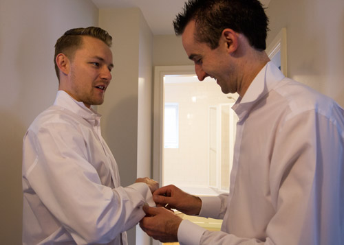 the groom and best man helping each other get ready on the morning of the wedding