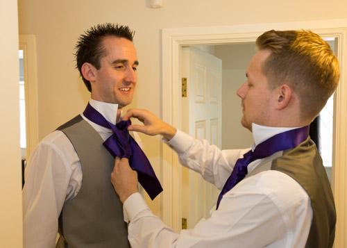 best man helping to tie the grooms cravat