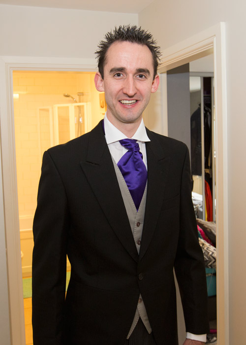 the groom in a black suit with grey waitcoat and purple cravat on the morning of the wedding